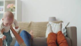 Het gelukkige moeder en vader spelen met baby thuis stock video
