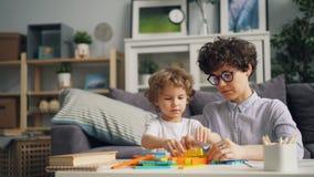 Het gelukkige moeder en zoons spelen met stuk speelgoed bakstenen die thuis van bouw genieten stock videobeelden