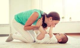 Het gelukkige moeder spelen met baby thuis stock foto