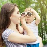 Het gelukkige moeder spelen met haar baby in het park Royalty-vrije Stock Foto's