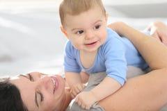 Het gelukkige moeder spelen met haar baby op het bed stock fotografie