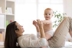 Het gelukkige moeder spelen met pasgeboren baby stock afbeelding