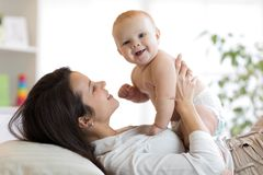 Het gelukkige moeder spelen met pasgeboren baby stock afbeeldingen