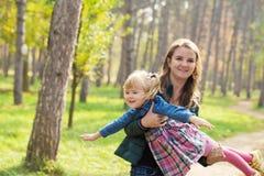 Het gelukkige moeder spelen met zijn dochter in het park in de zomerdag stock afbeeldingen