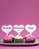 Het gelukkige Moederdagbericht op roze en wit verfraaide cupcakes - verticaal met exemplaarruimte Royalty-vrije Stock Foto's