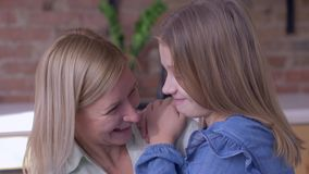 Het gelukkige moederschap, weinig glimlachend kindmeisje vertelt geliefde mum het fluisteren geheimen thuis in oor