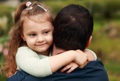 Het gelukkige mooie glimlachende jong geitjemeisje die haar vader met liefde koesteren overtreft stock foto's