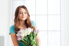 Het gelukkige mooie jonge boeket van de vrouwenholding van tulpen Stock Fotografie