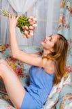 Het gelukkige mooie jonge slanke meisje zit op een bank in een coz Royalty-vrije Stock Foto's