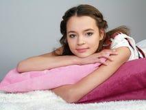 Het gelukkige mooie meisje ligt op roze hoofdkussens royalty-vrije stock afbeeldingen