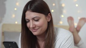 Het gelukkige mooie meisje in pyjama met lang haar gebruikt mobiele op bed liggen thuis en telefoon die glimlachen Close-up stock footage
