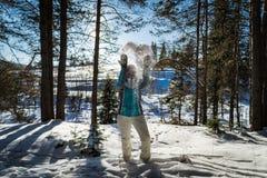 Het gelukkige mooie meisje spelen in de sneeuw tegen dag stock foto's