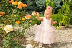 Het gelukkige mooie meisjesjonge geitje viert haar verjaardag met roze decor in mooie tuin De positieve menselijke vreugde van he Royalty-vrije Stock Fotografie