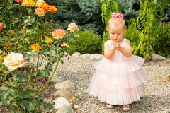 Het gelukkige mooie meisjesjonge geitje viert haar verjaardag met roze decor in mooie tuin De positieve menselijke vreugde van he Royalty-vrije Stock Afbeeldingen