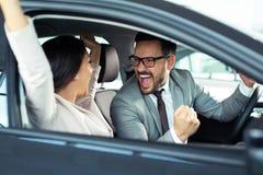 Het gelukkige mooie paar kiest een nieuwe auto bij het handel drijven stock afbeelding