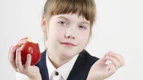 Het gelukkige mooie schoolmeisje eet grote rode appel stock footage