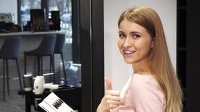 Het gelukkige mooie vrouw tonen beduimelt omhoog het zitten bij de kapperstudio stock fotografie