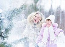 Het gelukkige mopther en jong geitje spelen met sneeuw in de winter Stock Foto