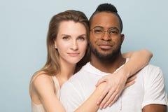Het gelukkige multiraciale paar bekijkt camera die samen stellen royalty-vrije stock afbeeldingen