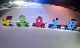 het gelukkige nieuwe jaar van 2018, houten stuk speelgoed trein het dragen aantallen van het jaar van 2018 op sneeuw Stuk speelgo Stock Foto