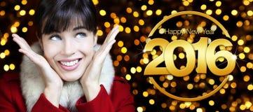 Het gelukkige nieuwe jaar 2016, vrouw kijkt omhoog op lichtenachtergrond Stock Afbeelding