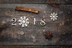 Het gelukkige Nieuwjaar 2018 echte houten cijfers met pijpjes kaneel, de sneeuwvlok en de anijsplant spelen op donkere houten ach Royalty-vrije Stock Afbeelding