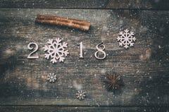Het gelukkige Nieuwjaar 2018 echte houten cijfers met pijpjes kaneel, de sneeuwvlok en de anijsplant spelen op donkere houten ach Royalty-vrije Stock Fotografie