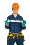 Het gelukkige niveau van de de holdingsbel van de bouwersvrouw Stock Fotografie