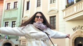 Het gelukkige onbezorgde jonge vrouw het glimlachen dansen en roes rond openlucht op Europese stadsstraat stock videobeelden