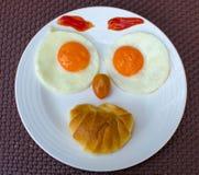 Het gelukkige ontbijt van Gezichts Bradende Eieren stock foto