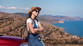 Het gelukkige ontspannen jonge reisvrouw genieten die op de hemel van de autobonnet bij achtergrond zonnebaden stock footage