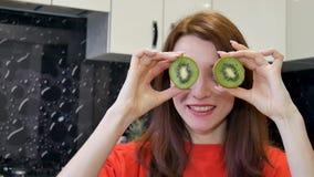 Het gelukkige opgewekte jonge vrouw spelen met rijpe kiwi alvorens voedsel bij de keuken voor te bereiden Positieve menselijke em stock video
