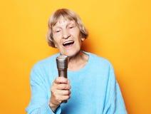 Het gelukkige oude hogere vrouw zingen met microfoon, die pret hebben, die muzikaal talent over gele achtergrond uitdrukken stock foto's