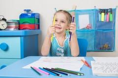 Het gelukkige oude meisje van vijf jaar kiest de correcte potloodtekening bij de lijst Stock Afbeeldingen