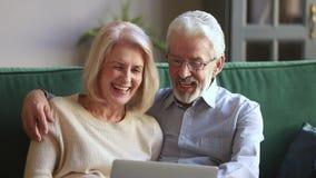 Het gelukkige oude paar spreken die doend Internet die gebruikend laptop winkelen lachen stock footage