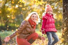 Het gelukkige ouder en jong geitje openlucht spelen met de herfst Royalty-vrije Stock Foto's