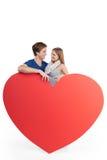 Het gelukkige paar is achter groot rood hart Stock Afbeeldingen