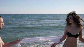 Het gelukkige paar bij oceaanstrand, het liefdepaar bij de zomerrust, de kerel en het meisje omhelzen zacht, jongerenflirt, Vrien stock footage