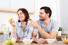 Het gelukkige paar brengt vrije tijd door of weekend samen bij keuken, stelt de blije echtgenoot vrouw voor om snack te eten, wei stock afbeeldingen