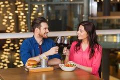 Het gelukkige paar die en drinkt wijn bij restaurant dineren Stock Fotografie