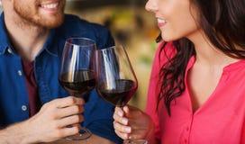 Het gelukkige paar die en drinkt wijn bij restaurant dineren stock foto