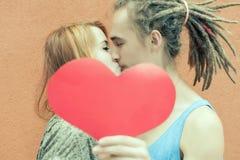Het gelukkige paar die van de Valentijnskaartendag rood hartsymbool houden Royalty-vrije Stock Foto