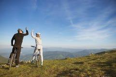 Het gelukkige paar gaat op een weg van het bergasfalt in het hout op fietsen met helmen die elkaar een hoogte vijf geven royalty-vrije stock foto
