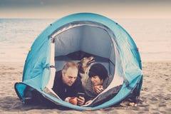 Het gelukkige paar geniet van technologie en vrijheid met een tent die bij het strand dichtbij het zeewater wordt geplaatst - alt stock afbeelding