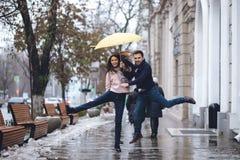 Het gelukkige paar, kerel en zijn meisje de gekleed in vrijetijdskleding springen onder de paraplu op de straat in de regen stock fotografie