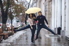 Het gelukkige paar, kerel en zijn meisje de gekleed in vrijetijdskleding springen onder de paraplu op de straat in de regen stock afbeeldingen