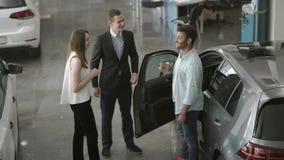 Het gelukkige paar kocht een moderne auto in autotoonzaal stock videobeelden