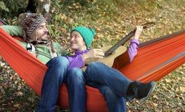 Het gelukkige paar koelen in hangmat in de herfst het bosvrouw spelen Royalty-vrije Stock Afbeelding