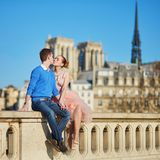 Het gelukkige paar kussen dichtbij Notre-Dame-kathedraal in Parijs stock fotografie