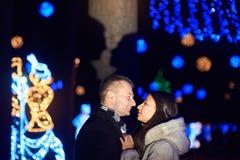 Het gelukkige paar kussen op de achtergrond van verlichting en bokeh stock fotografie